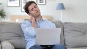 Przystojny młody człowiek z szyja bólem pracuje na laptopie zbiory