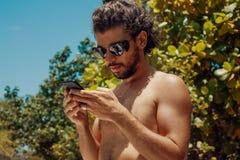 Przystojny młody człowiek z telefonem komórkowym outdoors zdjęcie royalty free