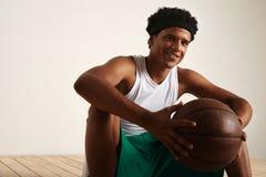 Przystojny młody czarny gracza koszykówki obsiadanie na drewnianej podłoga Zdjęcia Stock
