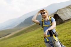 Przystojny młody czerwony włosiany mężczyzna wycieczkuje na górze z okularami przeciwsłonecznymi fotografia stock