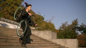 Przystojny młody dorosły mężczyzna jest ubranym czarnego przypadkowego mienia jego klasyczny bicykl na ramieniu podczas gdy chodz zbiory