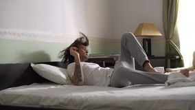 Przystojny młody facet skacze w łóżko i bierze pokrywę z koc w piżamach swobodny ruch zdjęcie wideo