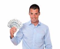 Przystojny młody facet trzyma jego dolary Obraz Stock