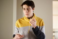 Przystojny młody facet w żółtym pulowerze trzyma telefon w jego rękach i patrzeje zamyślenie strona zdjęcie royalty free
