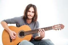 Przystojny młody męski gitarzysty obsiadanie i bawić się gitara akustyczna Obrazy Royalty Free