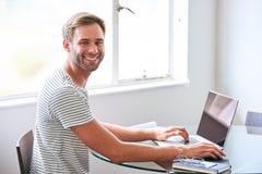 Przystojny młody męski uczeń ono uśmiecha się przy kamerą sadzającą za laptopem Obrazy Royalty Free