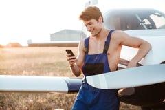 Przystojny młody mechanik w całkowitym trwanie wirh smartphone blisko samolotu obraz royalty free
