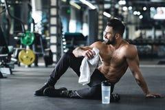 Przystojny młody mięśniowy sportowiec odpoczywa po treningu fotografia royalty free