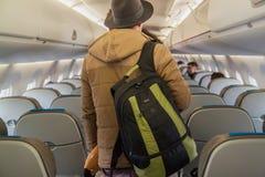Przystojny młody pasażer w ciepłej kurtki i kapeluszu stojakach z plecakiem w kabinie samolot fotografia royalty free
