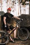 przystojny młody próbny rowerzysta oparty na skałach outdoors w lasowym i przyglądającym z powrotem obraz stock