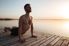 Przystojny młody sportowiec robi joga ćwiczeniom przy plażą obrazy royalty free