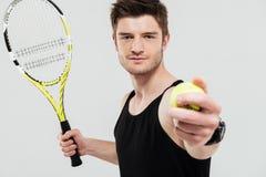Przystojny młody sportowiec trzyma tenisową piłkę i kant zdjęcia royalty free