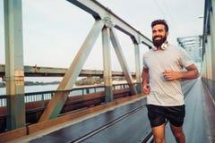 Przystojny młody szczęśliwy mężczyzna bieg przez most obrazy royalty free