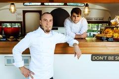 Przystojny młody szef kuchni patrzeje kamerę w karmowej ciężarówce Zdjęcie Royalty Free