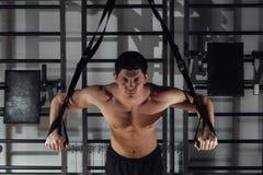 Przystojny młody umięśniony mężczyzna szkolenie z trx podczas gdy pracujący w gym out obraz royalty free