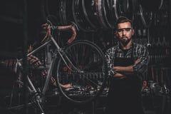 Przystojny m??czyzna w szk?ach stoi blisko niezmiennego bicyklu przy jego sw?j warsztatem fotografia royalty free