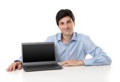 Przystojny młody biznesmen wystawia laptop Zdjęcie Stock