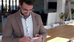 Przystojny m?ody biznesowy m??czyzna u?ywa jego smartphone w biurze podczas gdy siedz?cy na stole zbiory wideo