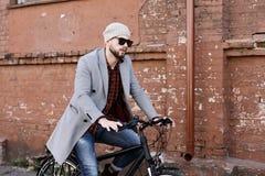 Przystojny m?ody cz?owiek jedzie rowerow? ulic? w mie?cie w popielatym ?akiecie i kapeluszu obraz stock