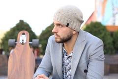 Przystojny m?ody cz?owiek siedzi w popielatym ?akiecie i kapeluszu z longboard, odpoczywaj?cy, Miastowy je?dzi? na deskorolce poj fotografia royalty free