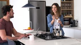 Przystojny m?ody cz?owiek u?ywa jego laptop i jej dziewczyny ?asowania jogurt w kuchni podczas gdy stoj?cy w domu zbiory wideo
