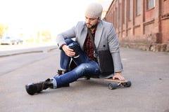 Przystojny m?ody cz?owiek w popielatym ?akieta i kapeluszu obsiadaniu na longboard na ulicie w mie?cie Miastowy je?dzi? na deskor zdjęcia stock