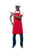 Przystojny męski szef kuchni pokazuje menu Zdjęcia Royalty Free
