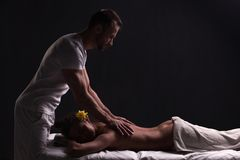 Przystojny masażysta robi masażowi dla brunetki kobiety zdjęcie stock
