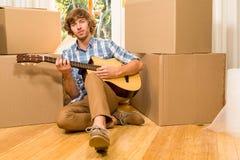 Przystojny mężczyzna bawić się gitarę z chodzeń pudełkami Zdjęcia Royalty Free