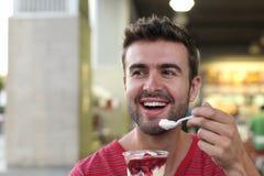 Przystojny mężczyzna je yummy lody Fotografia Stock