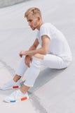 Przystojny mężczyzna obsiadanie w mieście na białym tle Zdjęcie Stock