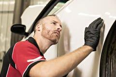 Przystojny mechanik opierający się na samochodzie w auto remontowym sklepie obraz stock
