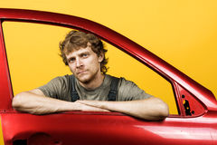 Przystojny mechanik przyglądający out samochodowego okno kolor żółty zdjęcia royalty free