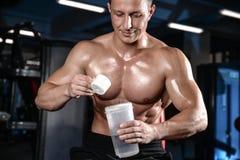 Przystojny mięśniowy bodybuilder mężczyzna robi ćwiczeniom w gym Zdjęcie Royalty Free