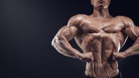 Przystojny mięśniowy bodybuilder pozuje na Frontowym Lat rozszerzaniu się Obrazy Stock