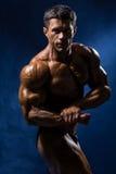 Przystojny mięśniowy bodybuilder pozuje nad błękitnym tłem Obrazy Stock