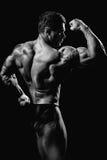 Przystojny mięśniowy bodybuilder pozuje nad błękitnym tłem Zdjęcie Stock