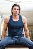 Przystojny, mięśniowy mężczyzna obsiadanie na biurku indoors, Zdjęcie Stock