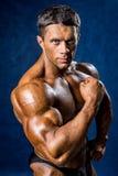 Przystojny mięśniowy mężczyzna pozuje nad błękitnym tłem Zdjęcia Stock