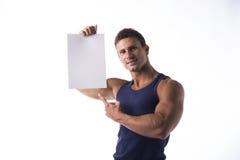 Przystojny mięśniowy mężczyzna wskazuje pusty znak Obraz Royalty Free