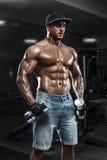 Przystojny mięśniowy mężczyzna z dumbbells pracującymi w gym out, robi ćwiczeniu Zdjęcia Royalty Free