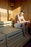 Przystojny, mięśniowy, młodego człowieka obsiadanie w sauna samotnym główkowaniu Obrazy Stock