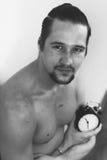 Przystojny, mięśniowy młody człowiek trzyma zegar, Obraz Royalty Free