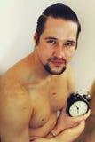 Przystojny, mięśniowy młody człowiek trzyma zegar, Obrazy Royalty Free
