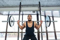 Przystojny mięśniowy weightlifter przy gym robi kucnięciom Zdjęcie Royalty Free