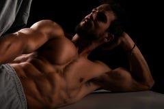 Przystojny mięśniowy wzorcowy lying on the beach na ławce Obraz Royalty Free