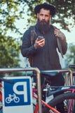 Przystojny modnisia podróżnik z elegancką brodą i tatuaż na jego rękach ubieraliśmy w przypadkowych ubraniach i kapeluszu, używać fotografia stock