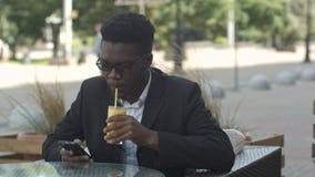 Przystojny modny afro amerykański biznesowego mężczyzna porywający sok podczas gdy usinh smartphone w outside kawiarni Zdjęcie Stock