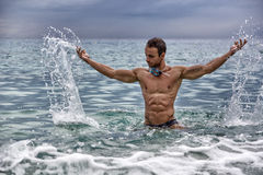 Przystojny młody bodybuilder w morzu, bryzga wodę up Obrazy Stock