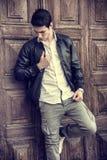 Przystojny młody człowiek przed drewnianym drzwi Zdjęcie Royalty Free